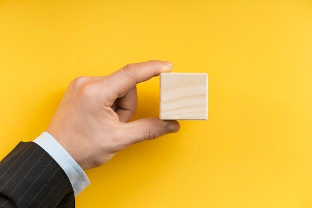 Homem segurando um cubo de madeira em branco