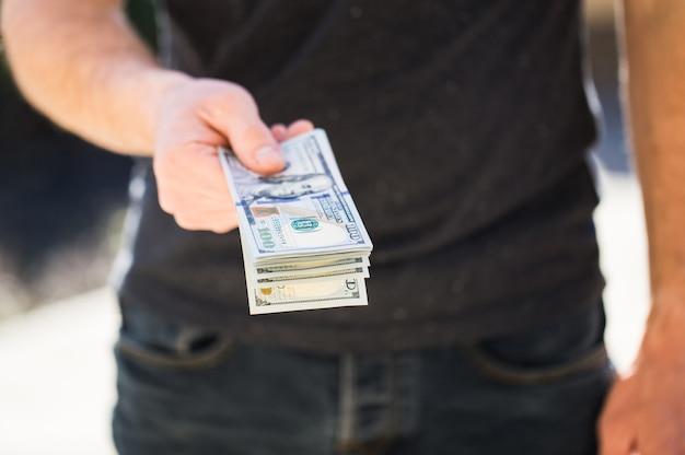 Homem segurando um dólar nas mãos