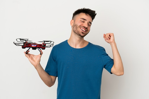 Homem segurando um drone isolado no fundo branco, comemorando uma vitória