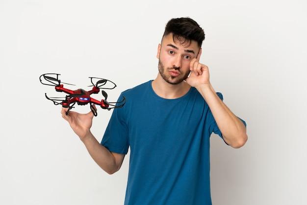 Homem segurando um drone isolado no fundo branco, pensando em uma ideia