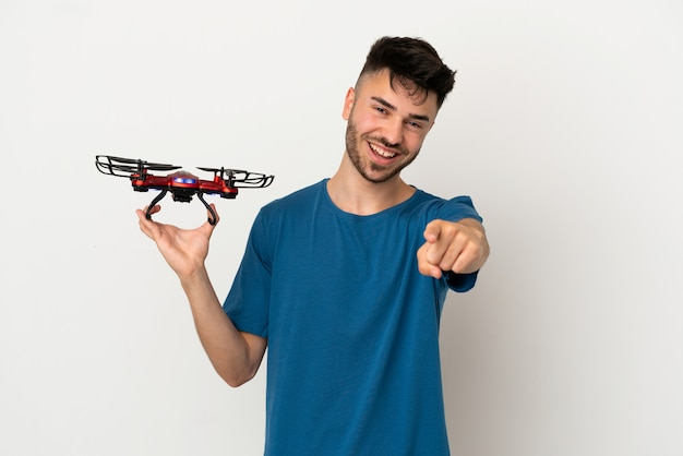 Homem segurando um drone isolado no fundo branco surpreso e apontando para a frente