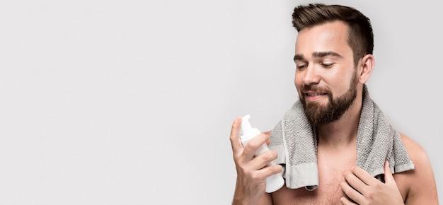 Homem segurando um frasco de creme de barbear com espaço de cópia