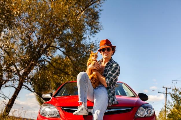 Homem segurando um gato fofo na frente do carro