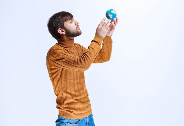 Homem segurando um globo do mundo minimalista.