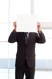 Homem segurando um grande cartão de visita na frente de seu rosto