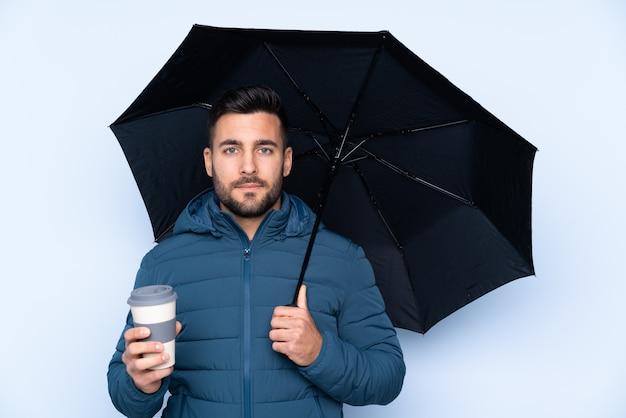 Homem segurando um guarda-chuva sobre parede isolada