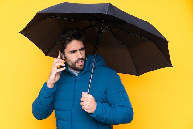 Homem segurando um guarda-chuva sobre parede