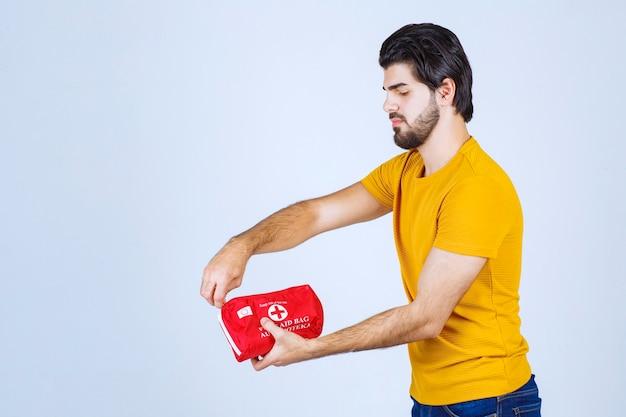Homem segurando um kit de primeiros socorros e abrindo o zíper.
