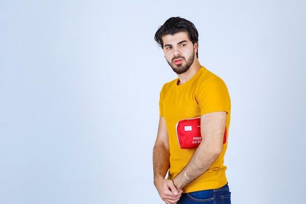 Homem segurando um kit vermelho de primeiros socorros debaixo do braço.