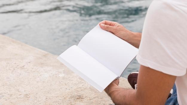 Homem segurando um livro à beira do lago com espaço de cópia