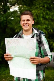 Homem segurando um mapa na floresta
