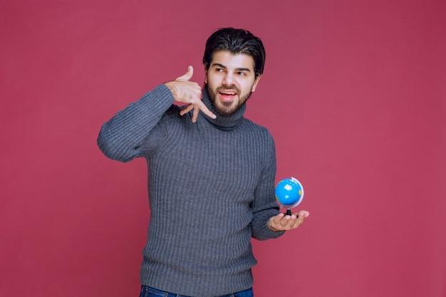 Homem segurando um mini globo azul e fazendo um indicativo de chamada.