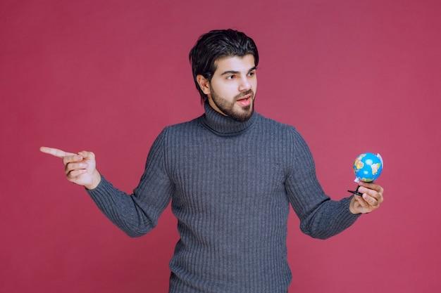 Homem segurando um mini globo e apontando para a esquerda. Foto gratuita