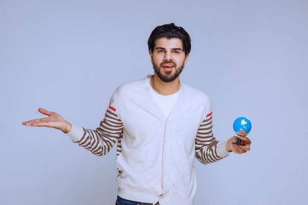 Homem segurando um mini globo e apontando para algo à esquerda.