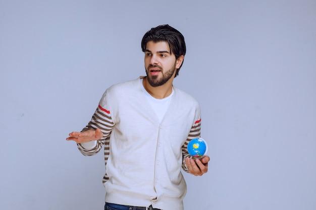 Homem segurando um mini globo e apontando para algo à esquerda. Foto gratuita