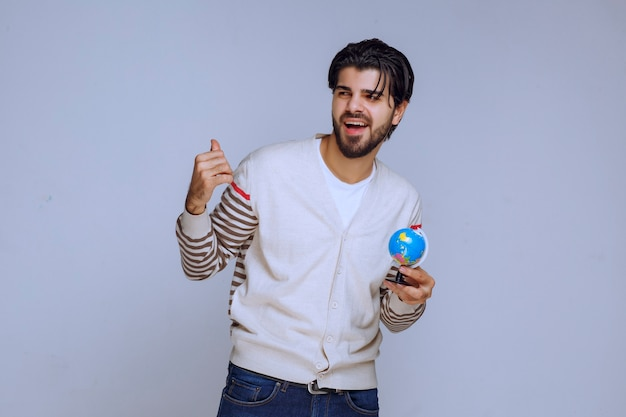 Homem segurando um mini globo e apontando para cima.