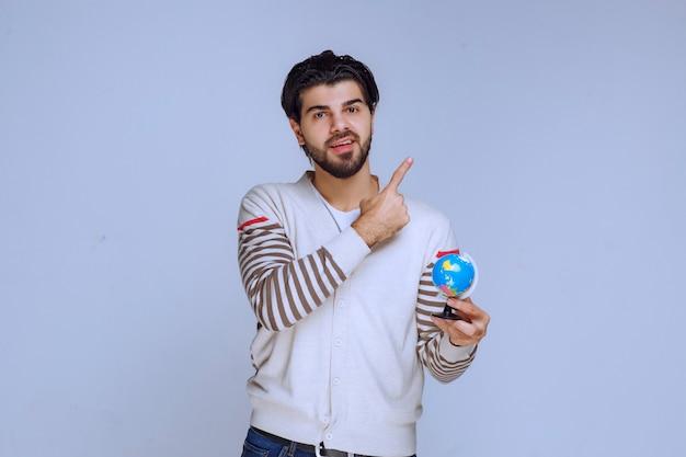 Homem segurando um mini globo e apontando para cima. Foto gratuita