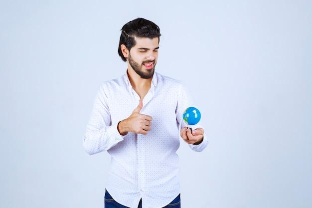 Homem segurando um mini globo e olhando para ele