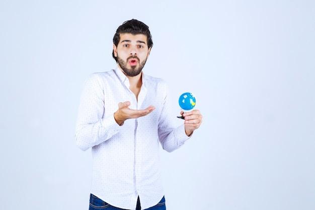 Homem segurando um mini globo e parece confuso