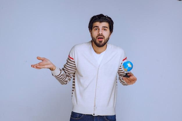 Homem segurando um mini-globo e parece não ter nenhum conhecimento de geografia.