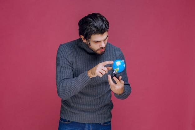 Homem segurando um mini globo e tentando encontrar um local lá.