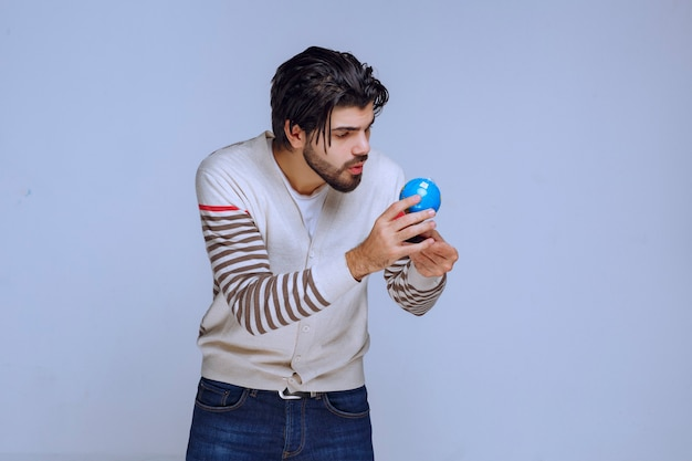 Homem segurando um mini globo e verificando-o cuidadosamente.