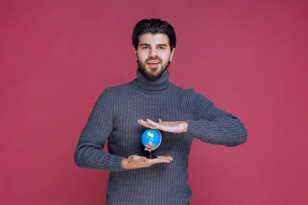 Homem segurando um mini globo entre as palmas das mãos.