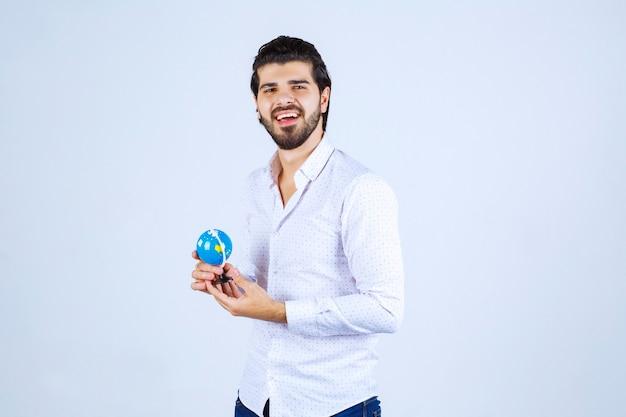 Homem segurando um mini-globo mundial