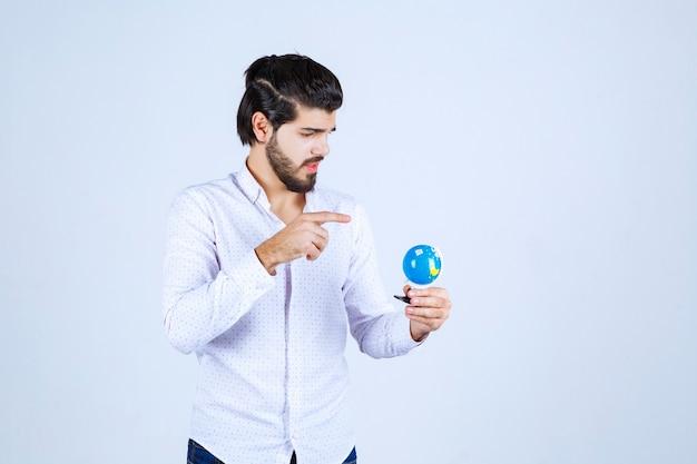 Homem segurando um minibundo e adivinhando um lugar nele