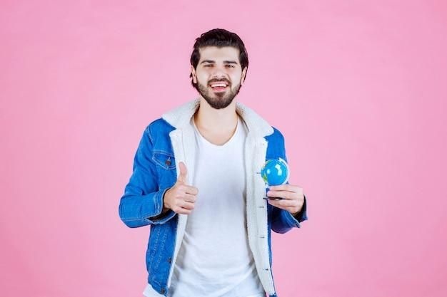 Homem segurando um minibundo e mostrando sinal de satisfação
