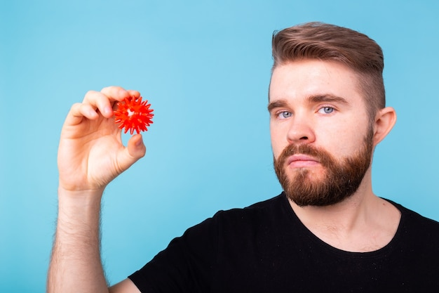 Homem segurando um modelo de coronavírus na parede azul