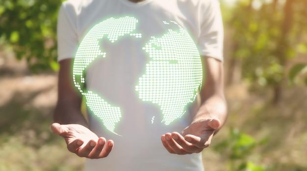 Homem segurando um mundo verde na natureza