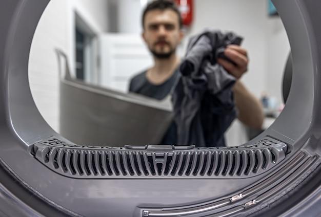 Homem segurando um pano sujo na vista de mão dentro da máquina de lavar.