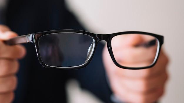 Homem segurando um par de óculos com moldura preta