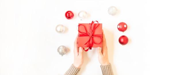 Homem segurando um presente de natal colocado sobre um fundo de mesa branco