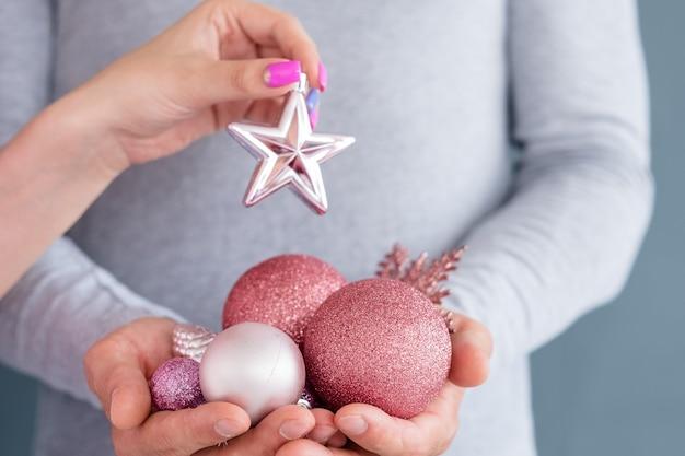Homem segurando um punhado de brinquedos sazonais tradicionais. ouro rosa enfeites brilhantes floco de neve pinho. mão de uma mulher segurando uma estrela.