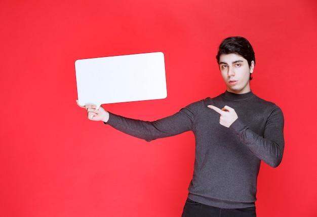 Homem segurando um quadro de ideias retangular e apontando para os participantes
