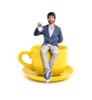 Homem segurando um relógio na xícara de café