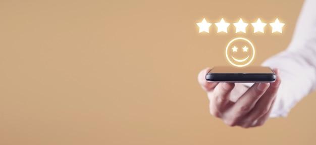 Homem segurando um rosto sorridente e cinco estrelas. comentários. satisfação do cliente