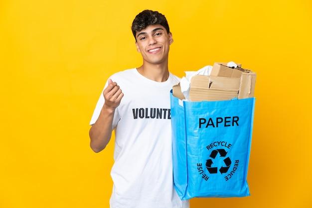 Homem segurando um saco de reciclagem cheio de papel para reciclar sobre amarelo isolado fazendo gesto de dinheiro