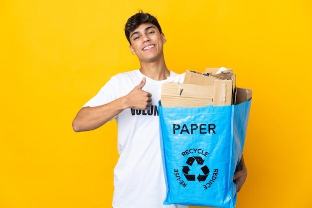 Homem segurando um saco de reciclagem cheio de papel para reciclar sobre amarelo isolado fazendo um gesto de polegar para cima