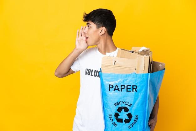 Homem segurando um saco de reciclagem cheio de papel para reciclar sobre amarelo isolado gritando com a boca aberta para o lado