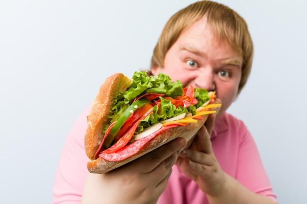 Homem segurando um sanduíche gigante