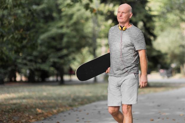 Homem segurando um skate de vista lateral