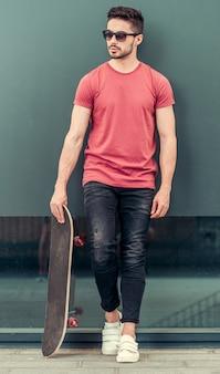 Homem segurando um skate na mão.
