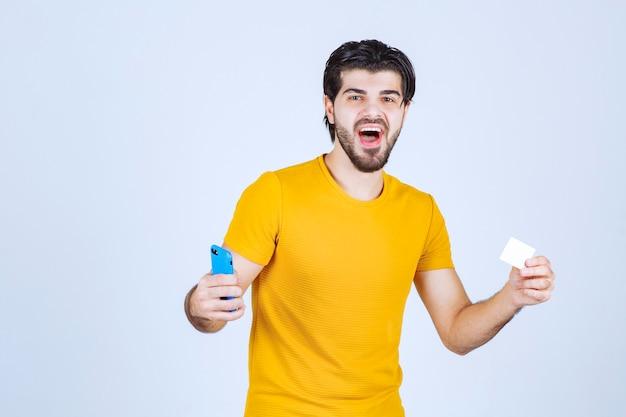 Homem segurando um smartphone azul e verificando suas mensagens ou ligando para o número de contato no cartão de visita.