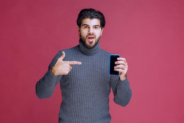 Homem segurando um smartphone e apresentando-o aos clientes.