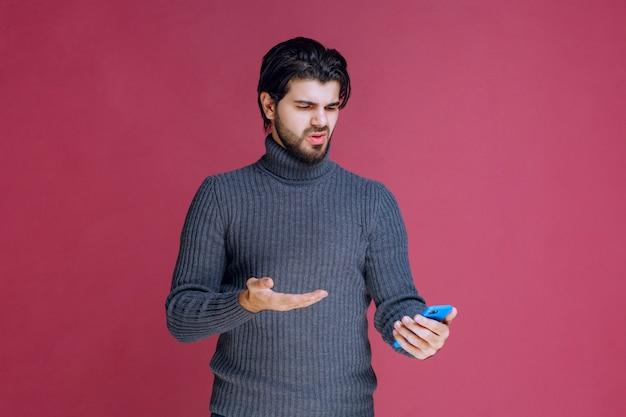 Homem segurando um smartphone e tentando entender suas funções.