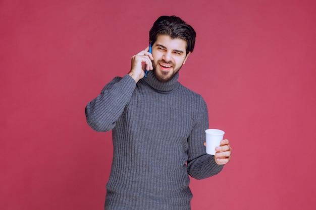 Homem segurando um smartphone e uma xícara de café e conversando.