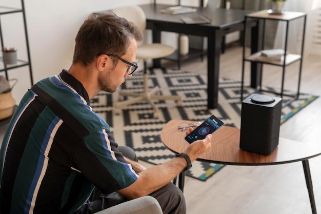 Homem segurando um smartphone enquanto usa um alto-falante inteligente